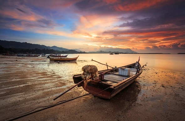 sunset in Langkawi Malaysia with fishing boats on beach