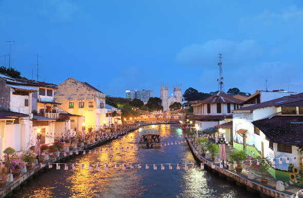 The twinkling lights of Malacca on either side of the river.