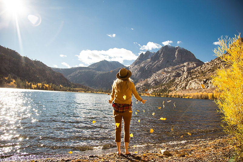 A woman stands on the shore amid autumn leaves at Silver Lake, California