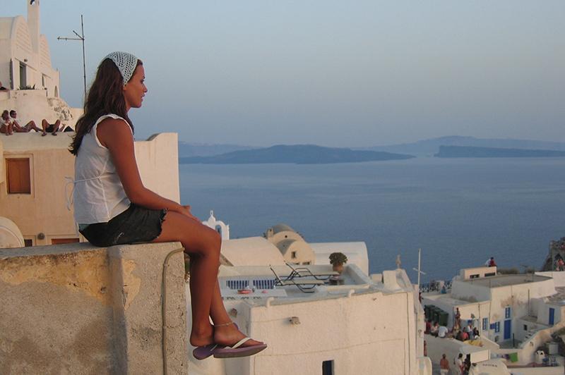 A woman watches the sun set in Oia, Santorini.