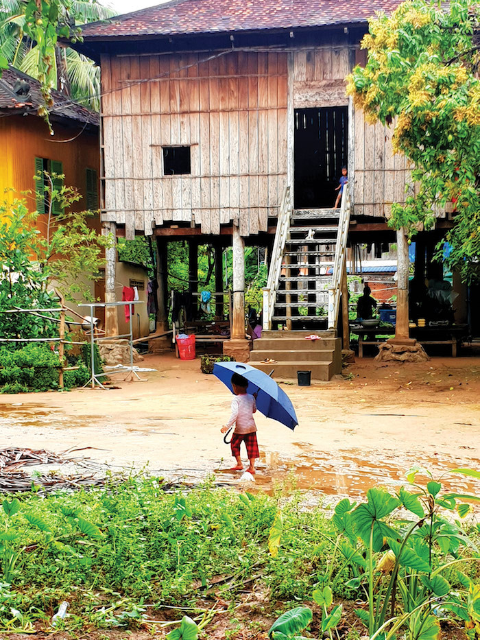 Child dances in the rain in Angkor Bon, a remote Cambodian village in Kampong Chhang province - Mekong River cruise