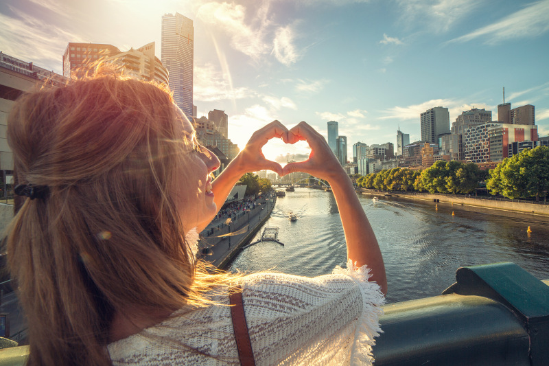 A girl making a loveheart with Melbourne city in the background