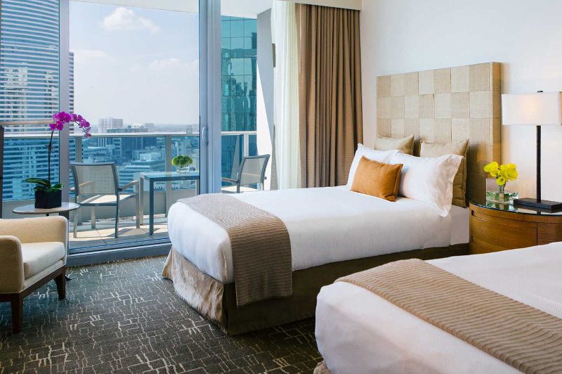 A guestroom at the Kimpton EPIC Miami, with a view out to the balcony and the CBD.