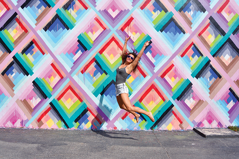 A young woman jumps in front of a street art mural in Miami's Wynwood Walls.