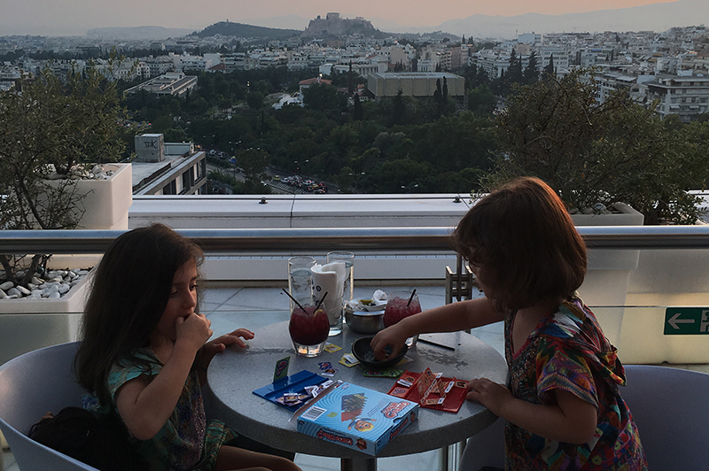 Two little girls sit on a hotel balcony with the Acropolis in the background.