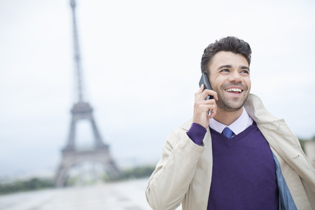 A smiling businessman in front of the Eiffel Tower.