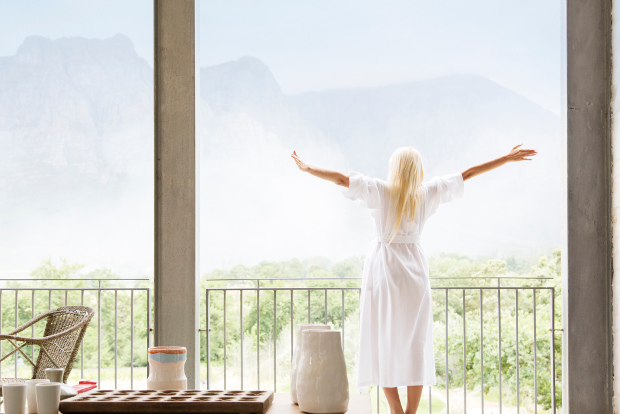 A woman stretches on her balcony in the morning.