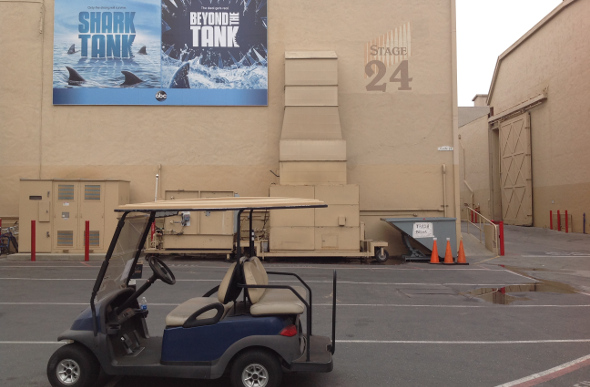 A buggy in the Sony Pictures back lot, with Shark Tank posters in the background.