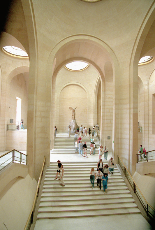 The statue of the Winged Victory of Samothrace stands at the top of a flight of stairs at the Louvre, in Paris.