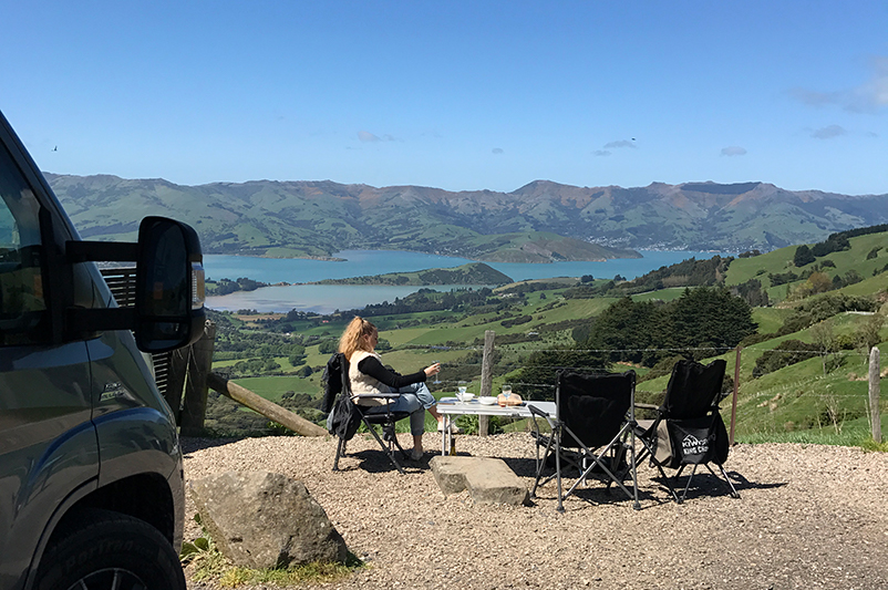 Teen girl sits by the road in New Zealand.