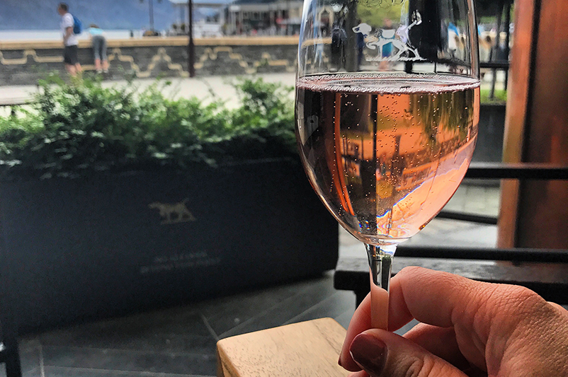 Holding a glass of sparkling wine in Queenstown.