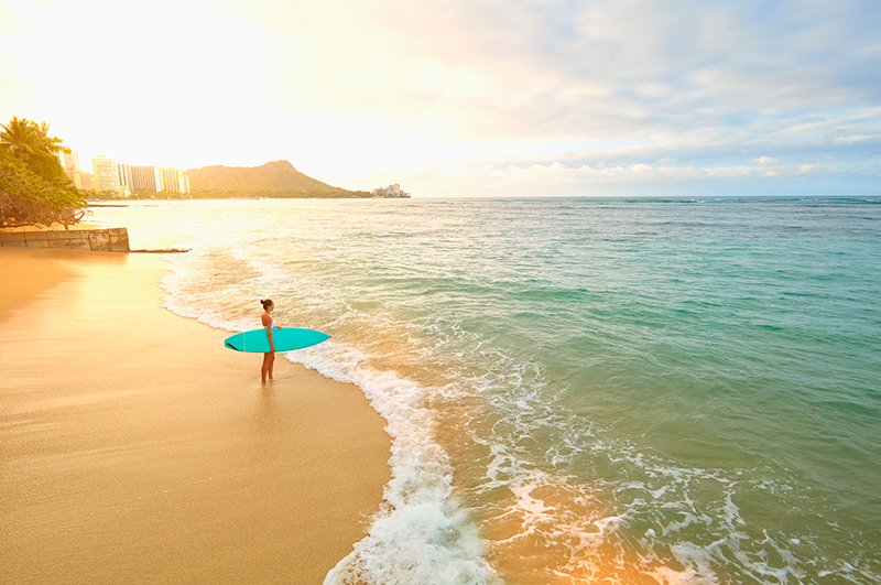 Woman with surfboard on Waikiki Beach