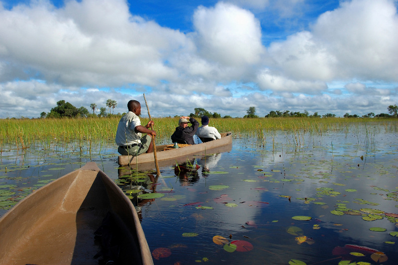 Three people in a traditional dug-out canoe on the Okavango Delta, Botswana