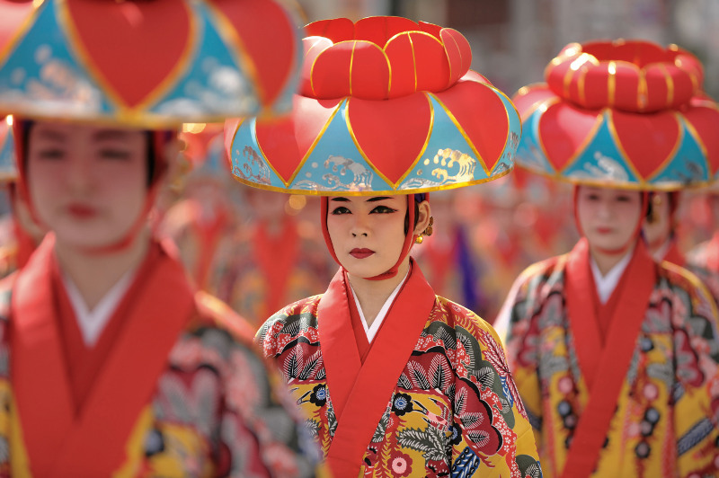 A woman wears a traditional bingata kimono and lotus-flower headpiece for a festival performance. Image: Getty
