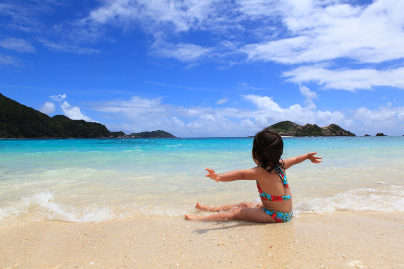 A child sits on the sand, stretching out her arms, at a beach in Okinawa's Kerama Islands.