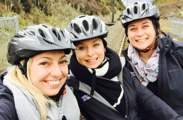 A group of girls smiling and wearing helmets