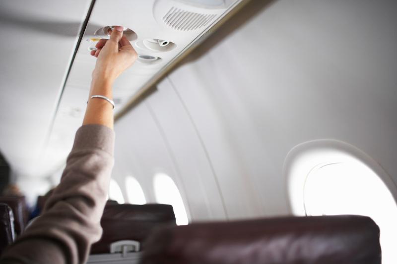 A person reaching for their air vent on an airplane