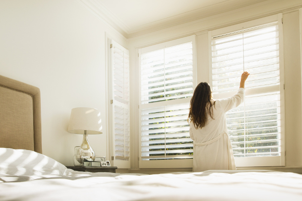 Woman opens blinds in morning
