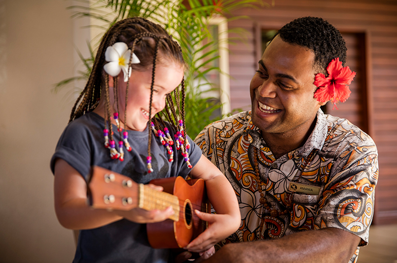 A hotel staff member and young guest at Outrigger Fiji Beach Resort