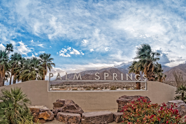 A palm spring sign with the mountains in the background