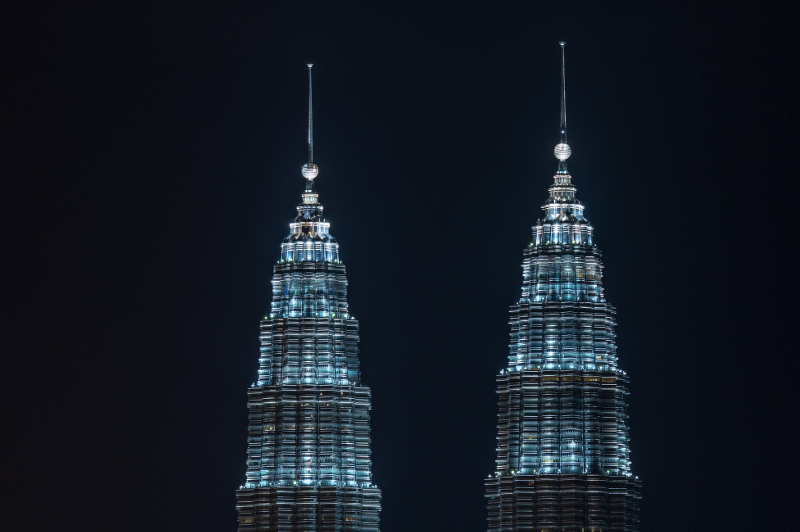 The illuminated spires and ring balls of Kuala Lumpur's Petronas Twin Towers are illuminated at night.