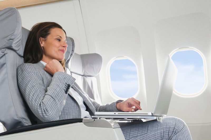 A woman using a laptop on the plane