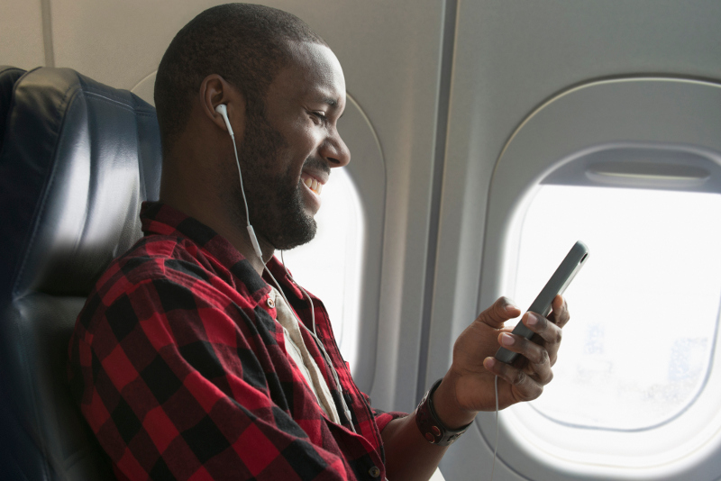 A smiling man listening to something on his phone
