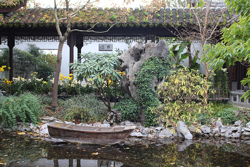 Portland's Lan Su Chinese Garden lake in November with autumn leaves and a boat