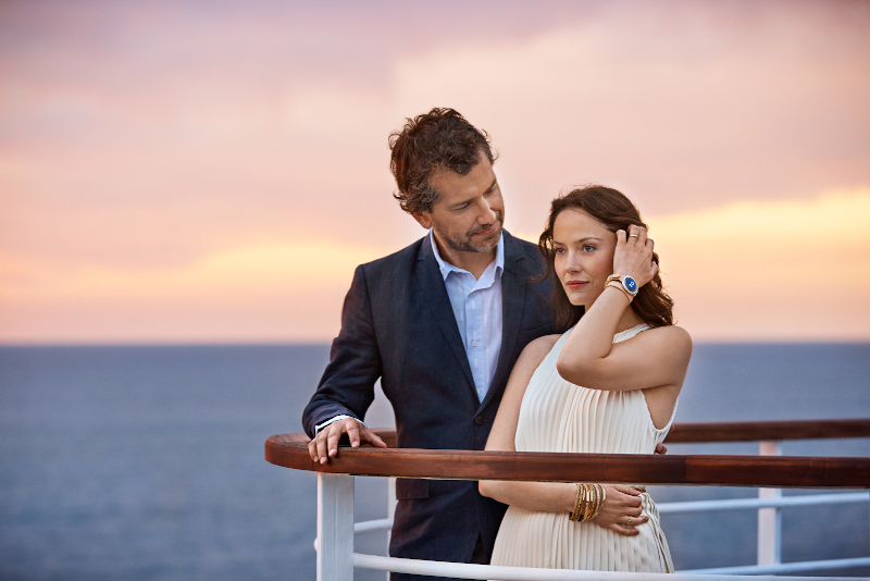 A couple standing at the back of a cruise ship as the sunsets. They are wearing the medallions
