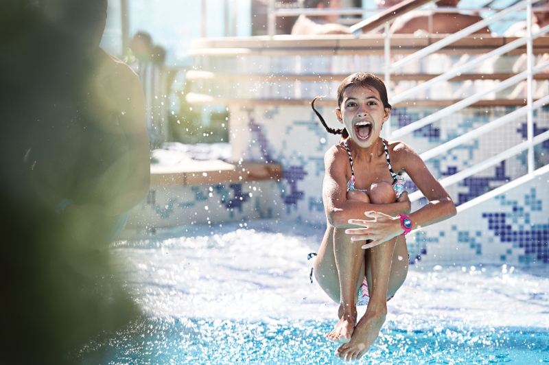 A kid jumping into the pool on board. She is wearing a medallion as a wrist band