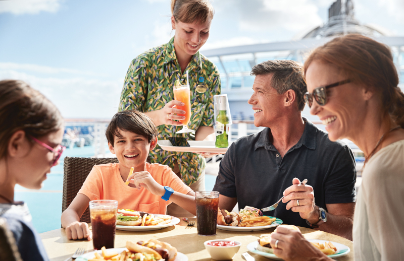 A family sitting around a table having lunch on board. They are wearing the medallions on their wrists