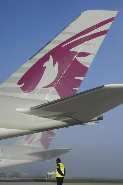 The Qatar logo on the tail of an airplane