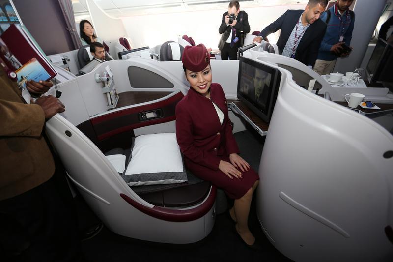 flight attendant sitting on business class seat qatar airways