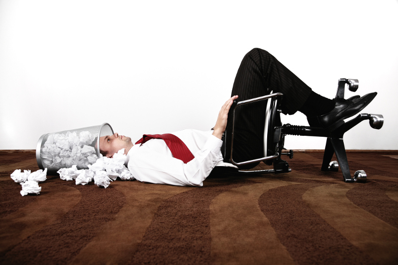 A businessman lies on his back with his head in a waste paper basket.