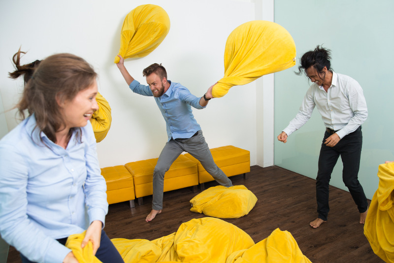 Three people engage in a beanbag fight.