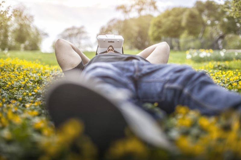 A man wearing virtual reality goggles lies in a field of yellow flowers.