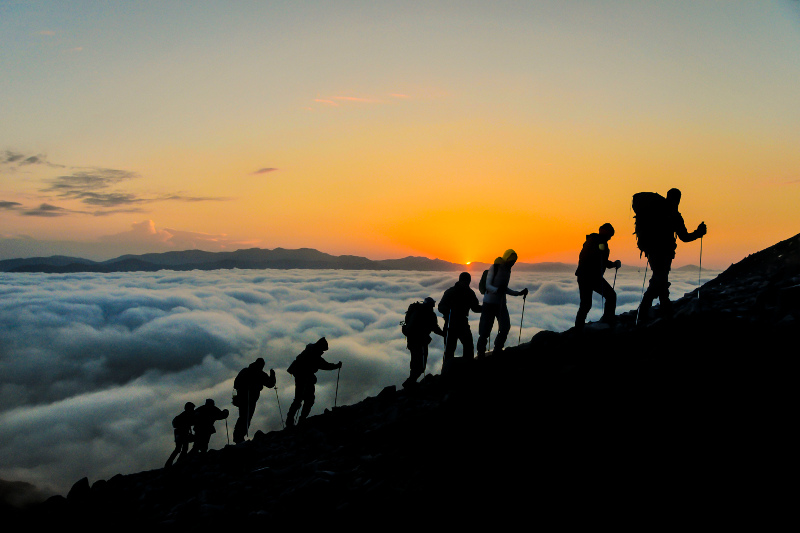 A row of mountain climbers scaling a peak.