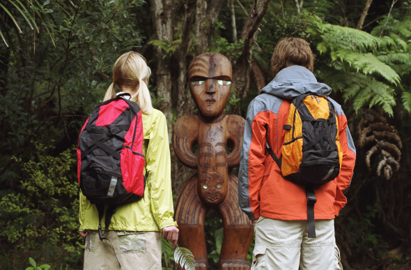 A couple standing in front of a Maori carving