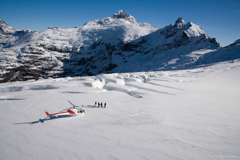 people and helicopter in snow new zealand
