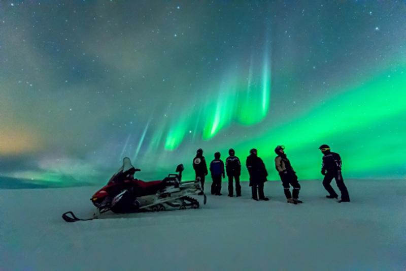 snowmobiles under northern lights Finland