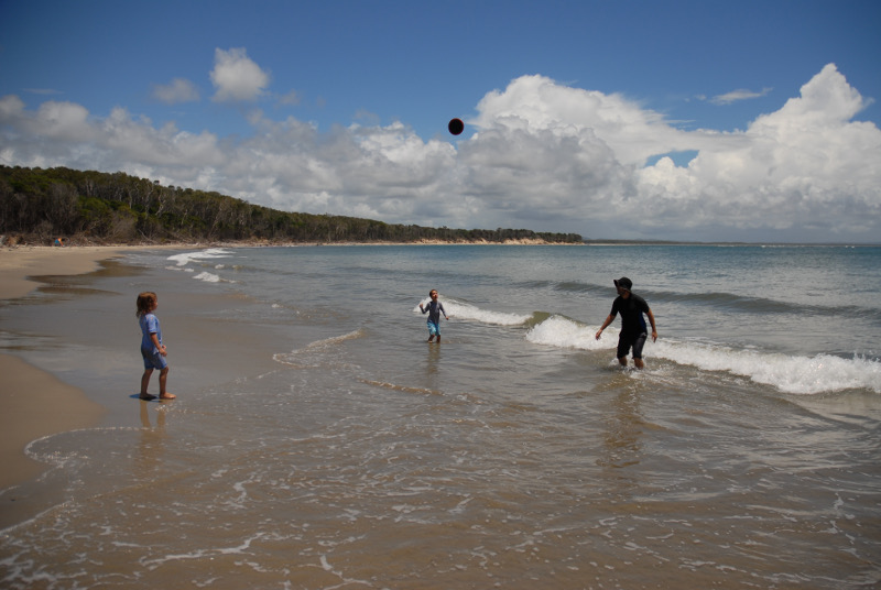 family playing frisbee on beach at iluka, new south wales
