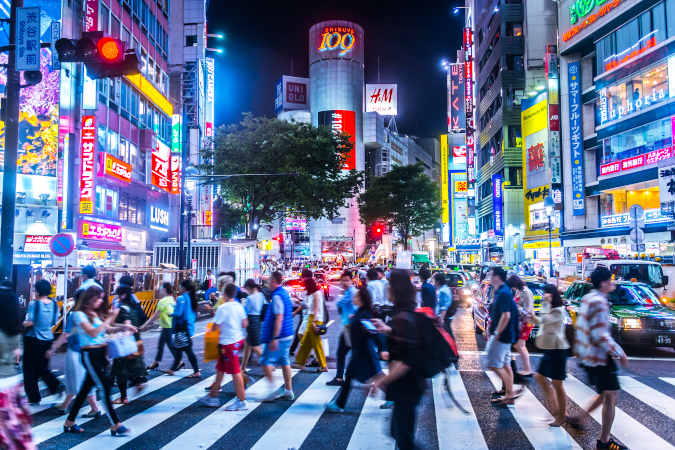 a busy crossing in tokyo with lots of lights and colours from the ads