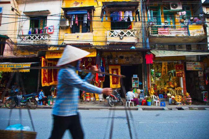 a Vietnamese man walking in a colourful vetnamese street