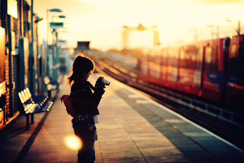 girl with camera on train station