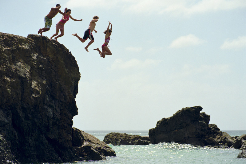 Friends leap off rock at Te Arai Point, North Island, New Zealand.