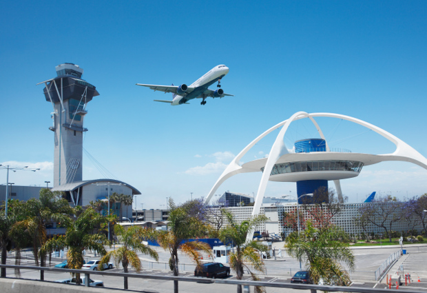 Theme building, control tower and plane taking off over LAX