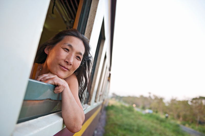 asian woman with head out of window of train