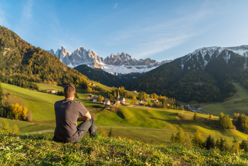 young man sitting on hill top, south tyrol