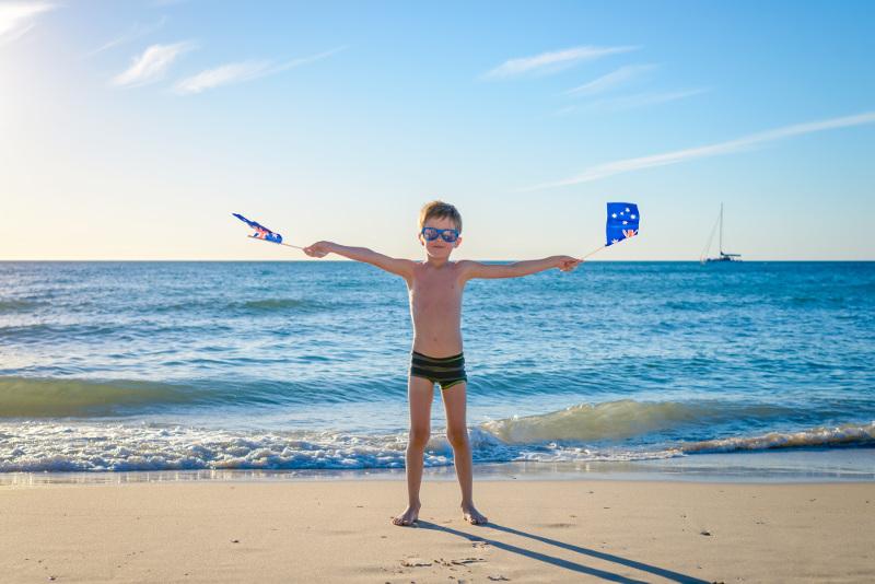 boy on beach with australia day flags