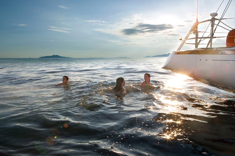 friends in sea near yacht, france